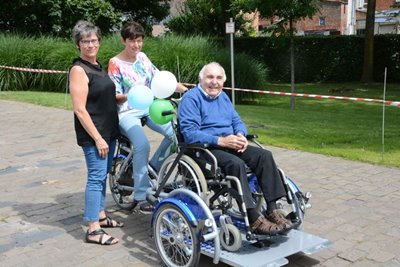 Residents and volunteers residential care facility use a wheelchair bike VeloPlus